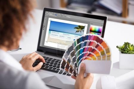 Photo for Close-up Of A Female Designer Holding Colorful Swatch Working On Laptop In Office - Royalty Free Image
