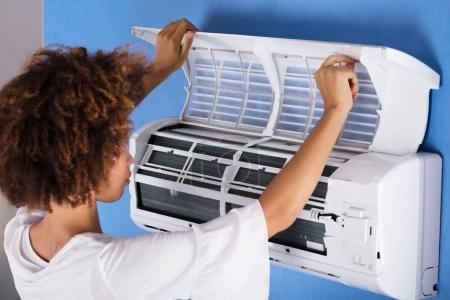 Close-up Of A Young Woman Checking Air Conditioner At Home