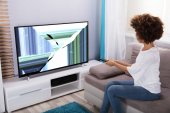 Young Woman Sitting On Sofa Near Television Showing Distorted Screen