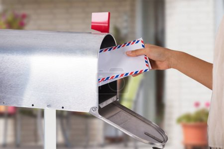 Close-up Of A Person's Hand Removing Letter From Silver Mailbox