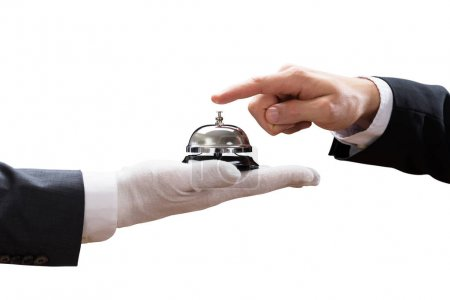Close-up Of Person's Hand Ringing Service Bell Held By Waiter On White Background