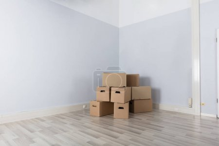 Empty Room With Stack Of Cartons On Floor