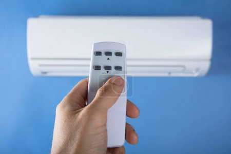 Close-up Of Man's Hand Adjusting Temperature Of Air Conditioner Using Remote