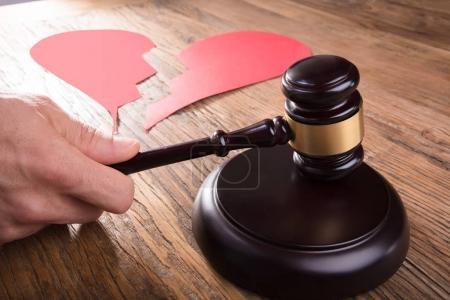 Cropped Image Of Divorce Judge With Broken Heart At Desk Hitting Gavel In Courtroom