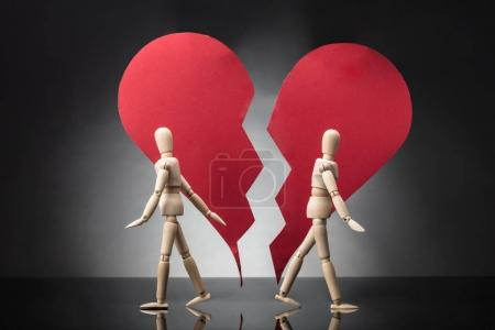 Two Wooden Dummy Standing Against Each Other With Broken Red Heart On Grey Background