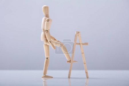 Wooden Figure Climbing Ladder On White Background