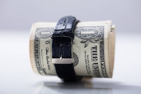Rolled Up Dollar Banknote Tied With Belt Against White Background