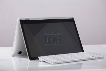 Photo for Close-up Of Blank Hybrid Laptop With External Over The White Desk At Workplace - Royalty Free Image
