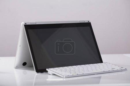 Photo pour Gros plan sur ordinateur portable blanc hybride avec externe au-dessus du bureau blanc au milieu de travail - image libre de droit