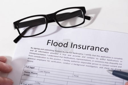 Elevated View Of Flood Insurance Form And Spectacles