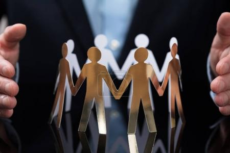 Close-up Of A Businessperson's Hand Protecting Paper Cut Out People On Desk
