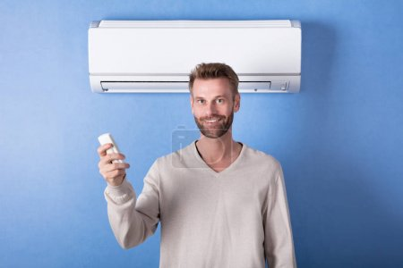 Happy Young Man Holding Remote Standing In Front Of Air Conditioner