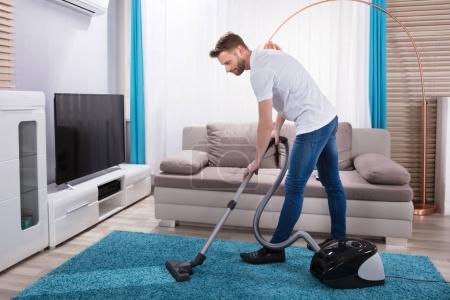 Young Man Cleaning Blue Carpet With Vacuum Cleaner...