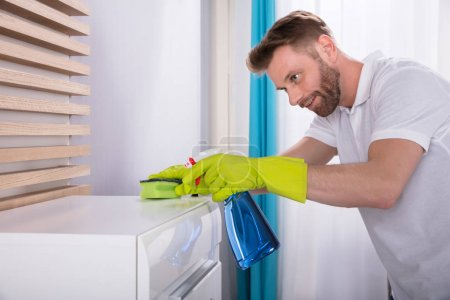 Smiling Young Man Cleaning Furniture With Spray Bottle At Home