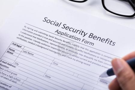 Close-up Of A Person's Hand Filling Social Security Benefits Application Form