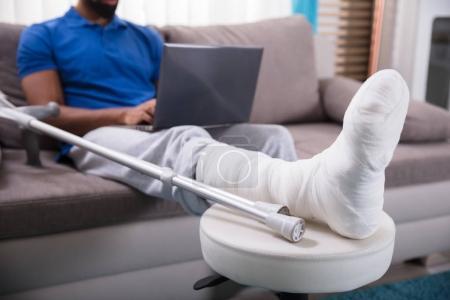 Photo pour Homme avec jambe cassée assis sur le canapé en utilisant un ordinateur portable - image libre de droit