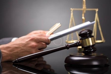 Close-up Of A Gavel In Front Of Judge Holding Document