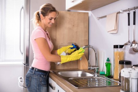 Happy Woman Cleaning Sink Tap In The Kitchen With Cloth And Spray Bottle