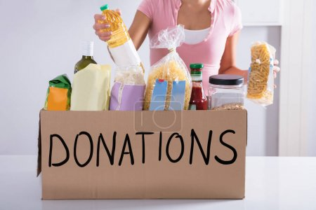 Midsection Of A Woman Putting Groceries In Donation Box On Table
