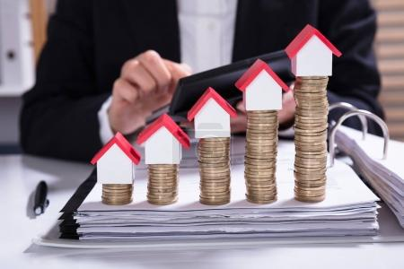 Midsection Of Businesswoman Calculating Invoice With House Models Arranged On Stacked Coins
