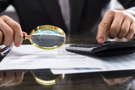 Close-up Of Businessperson's Hand Calculating Bill With Magnifying Glass On Desk