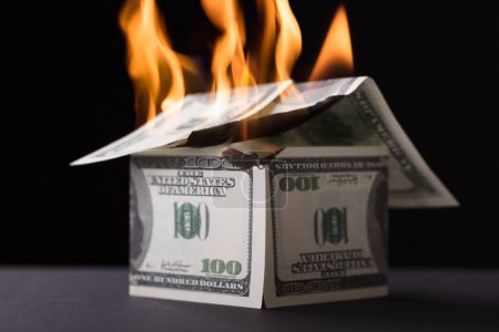 House Made Up Of Banknote Burning In Fire Against Black Background