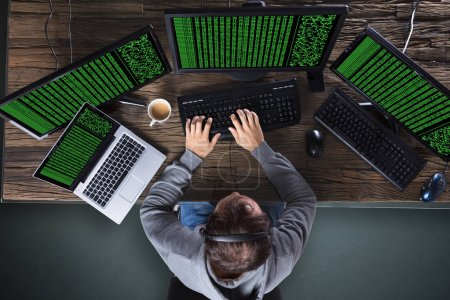High Angle View Of Hacker Stealing Data From Multiple Computer