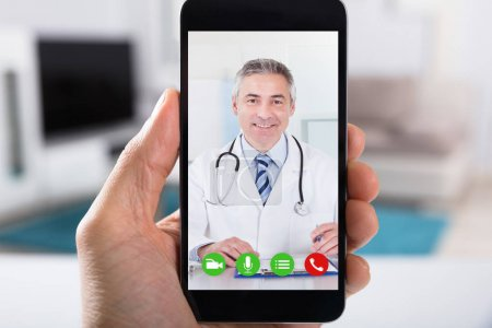 Close-up Of A Person Video Conferencing With Happy Male Doctor On Smartphone
