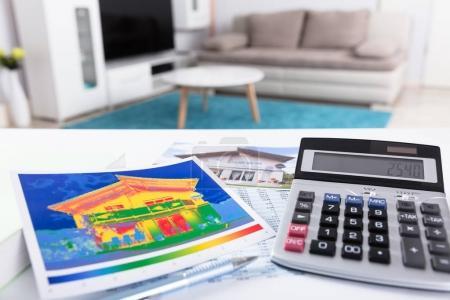 Foto de Primer plano de la pérdida térmica del hogar y la calculadora con números en la pantalla - Imagen libre de derechos