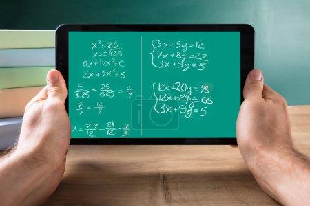 Photo pour Gros plan de la main d'une personne tenant une tablette numérique avec des équations mathématiques sur écran sur le Bureau - image libre de droit