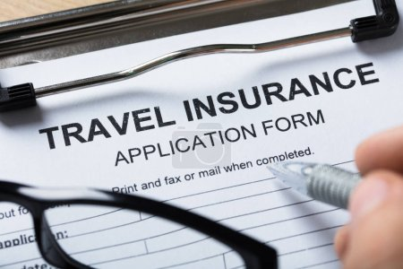 Close-up Of A Person's Hand Filling Travel Insurance Form With Pen