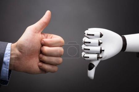 Foto de Empresario y robot mostrando el signo de pulgar hacia arriba y pulgar hacia abajo sobre fondo gris - Imagen libre de derechos