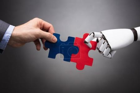 Businessperson And Robot Holding Jigsaw Puzzle On Grey Background