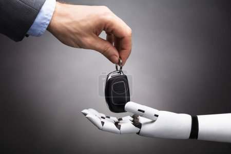 Close-up Of A Businessperson's Hand Giving Car Key To Robot On Grey Background