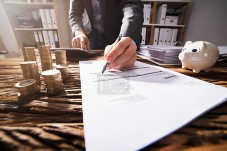 Close-up Of A Businessperson's Hand Signing Document With Stacked Golden Coins On Wooden Desk