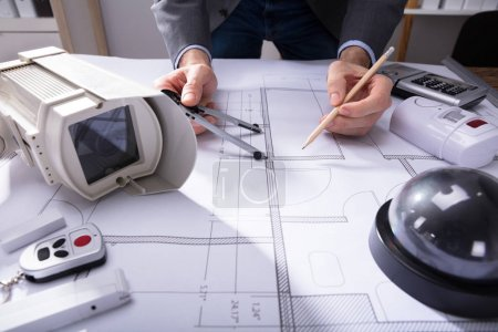Close-up Of An Architect's Hand Drawing Plan On Blueprint With Pencil
