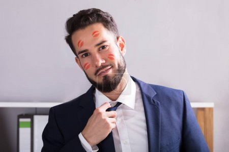 Close-up Of A Young Businessman With Lipstick Kiss Marks On Face