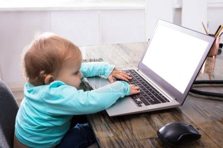 Baby Girl Using Laptop With Blank White Screen