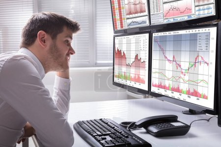 Side View Of A Sad Young Male Operator Looking At Graphs On Multiple Computer Screen