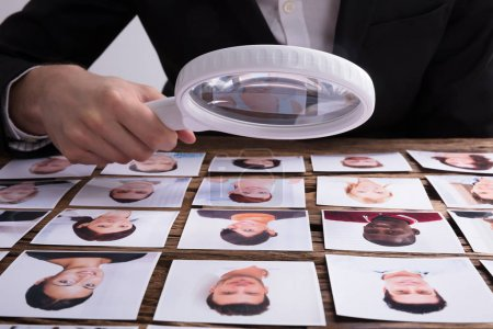 Close-up Of A Businessperson's Hand Looking At Candidate's Photograph With Magnifying Glass On Desk