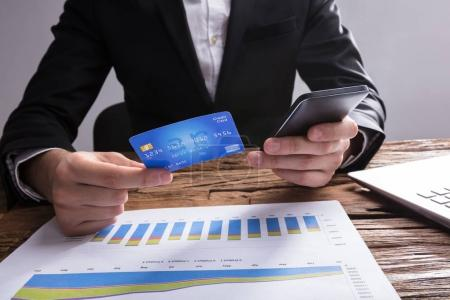 Close-up Of A Businessperson's Hand Shopping Online With Mobile Phone And Credit Card