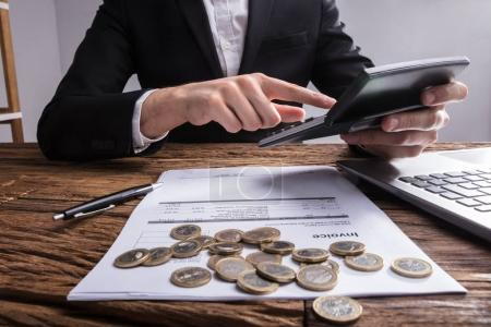 Businessperson's Hand Analyzing Bill With Coins On Wooden Desk