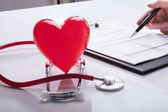 Stethoscope And Red Heart Near Doctor's Hand Analyzing Report On Clipboard