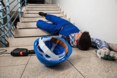 Foto de Handyman inconsciente acostado escalera con casco y taladro de piso - Imagen libre de derechos