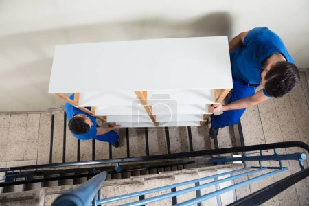 Photo for Close-up Of Two Young Men Carrying Wooden Shelf - Royalty Free Image