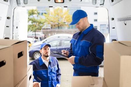 Photo for Young Male Mover Looking At His Partner Writing On Clipboard Near Cardboard Boxes - Royalty Free Image