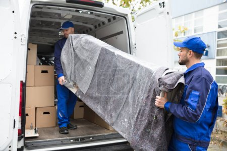 Photo for Two Young Delivery Men In Uniform Unloading Furniture From Vehicle - Royalty Free Image