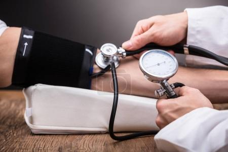 Close-up Of Doctor's Hand Checking Patient's Blood Pressure Over Wooden Table