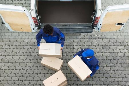 High Angle View Of Delivery Men Unloading The Cardboard Boxes From Truck