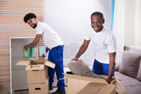 Smiling Young Movers Unpacking The Cardboard Boxes In The Home